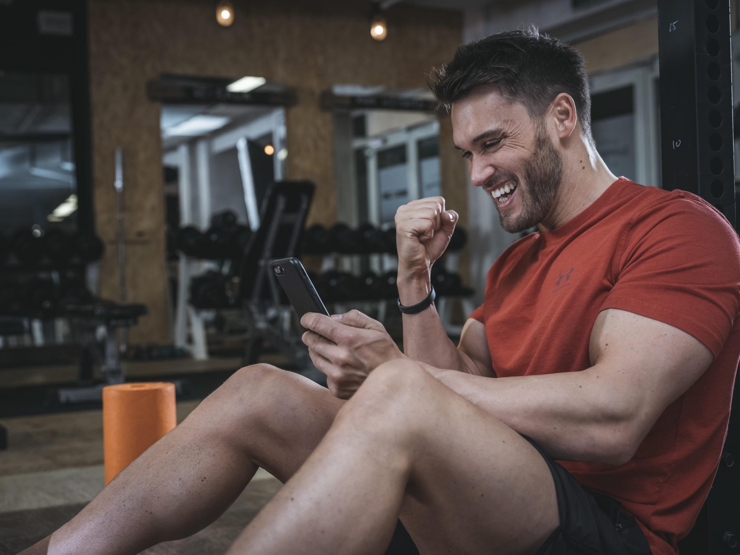 Mario Klintworth schaut auf sein Handy und freut sich über seine ALL IN Erfolge