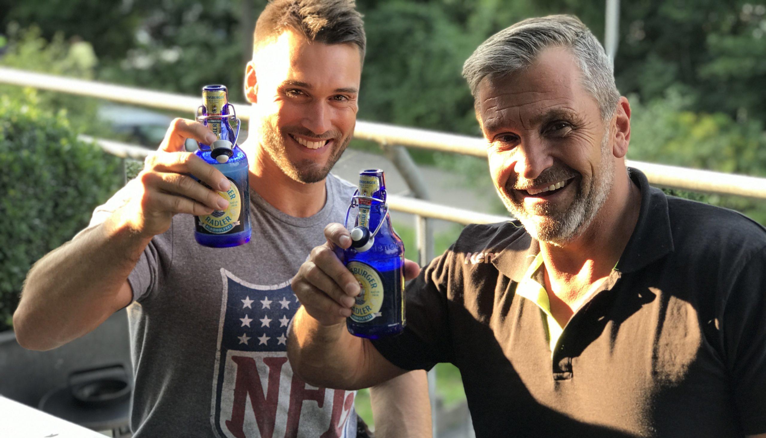 Zwei Männer stossen mit Bier an