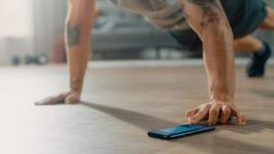 Trainingsprogramme Mann mit Handy im Fitnessstudio